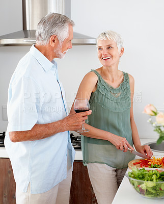 Buy stock photo Mature woman preparing salad while her husband is having wine