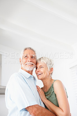 Buy stock photo A smiling aged couple embracing eachother