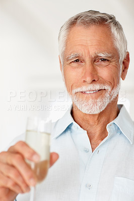 Buy stock photo Portrait of a happy old man holding a glass of champagne on a background