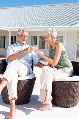 Buy stock photo Old couple enjoying a glass of champagne outdoors with their house at the back
