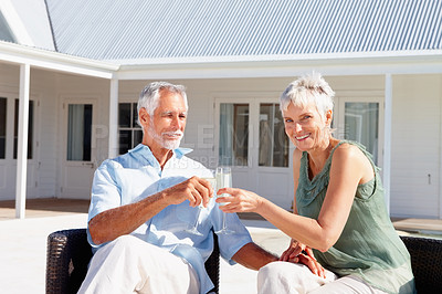 Buy stock photo Mature couple enjoying a glass of champagne outdoors with their house at the back