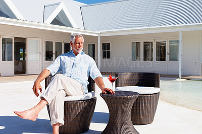 Buy stock photo Portrait of a retired man sitting on designer outdoor furniture with a martini outside his house