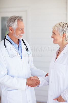 Buy stock photo Portrait of two successful senior doctors shaking hands with each other