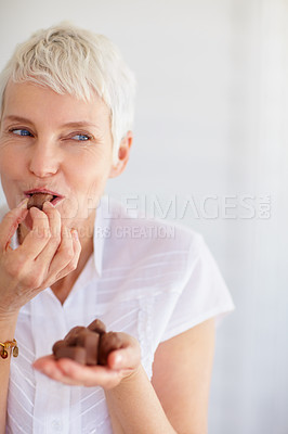 Buy stock photo Happy mature woman eating chocolates