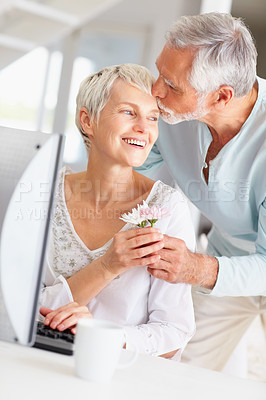 Buy stock photo Portrait of a senior man giving flower to wife while she's working on computer