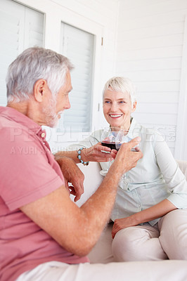 Buy stock photo Happy old couple having a glass of wine while enjoying at home