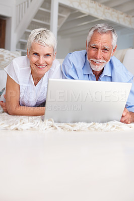 Buy stock photo Portrait of an aged old couple relaxing with laptop in front