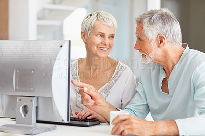 Buy stock photo A senior man teaching a senior woman how to use the computer