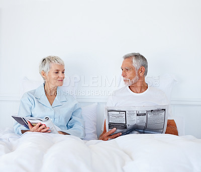 Buy stock photo Retired couple in bed reading the morning newspaper