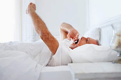 Buy stock photo Yawning old man stretching his arms in bed