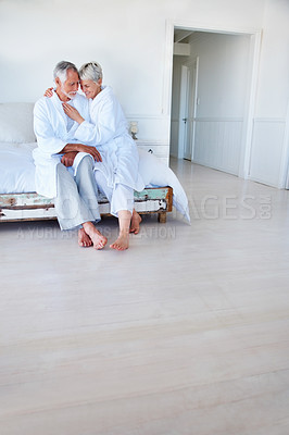 Buy stock photo A romantic senior mature couple sitting in the bed room and smiling