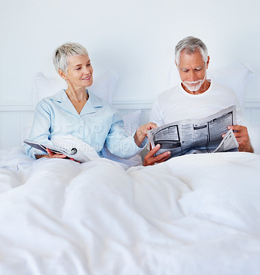 Buy stock photo Senior couple in bed reading the daily newspaper