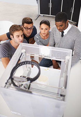 Buy stock photo Shot of a group of designers looking at a 3D printer
