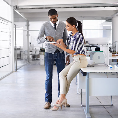 Buy stock photo Shot of two colleagues working together on a digital tablet