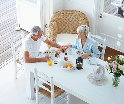 Buy stock photo An aged elderly couple enjoying their breakfast at home