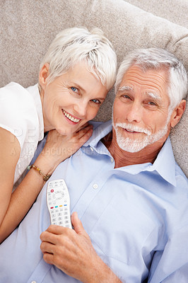 Buy stock photo Portrait of a couple lying down besides eachother with a remote control