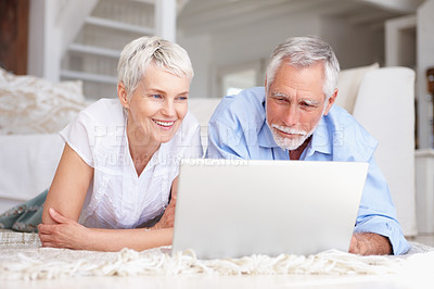 Buy stock photo Portrait of an attractive senior couple enjoying while working on a laptop