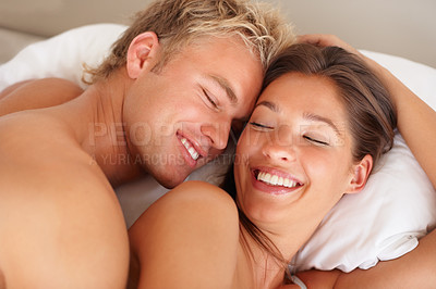 Buy stock photo Portrait of a young couple lying in bed smiling