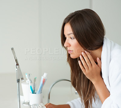 Buy stock photo Portrait of a young woman looking at her face in the mirror