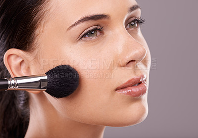 Buy stock photo Studio shot of a beautiful young woman applying makeup to her face