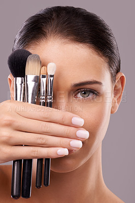 Buy stock photo A young woman holding makeup brushes against her face