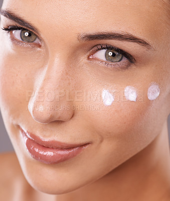 Buy stock photo Studio shot of a beautiful young woman with dots of a skincare product on her face