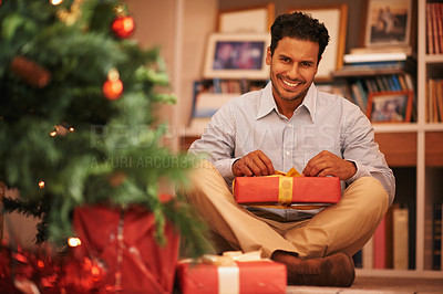 Buy stock photo Portrait of a young man sitting next to the tree opening christmas presents