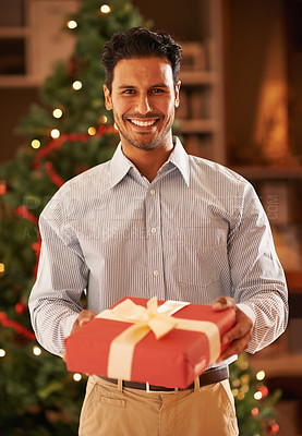 Buy stock photo Cropped shot of a young man holding a christmas present