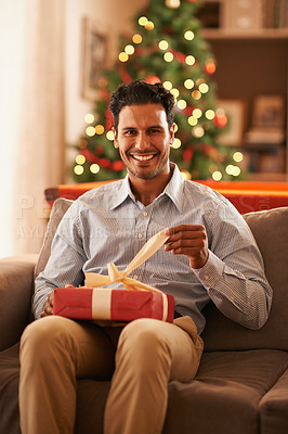 Buy stock photo A handsome young man sitting on a sofa opening a christmas present