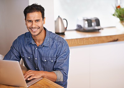 Buy stock photo Portrait of a handsome man working on his laptop while sitting in the kitchen