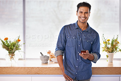Buy stock photo Portrait of a handsome holding a mobile phone while standing in the kitchen