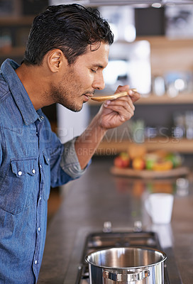 Buy stock photo Shot of a handsome man tasting food while he's cooking at home
