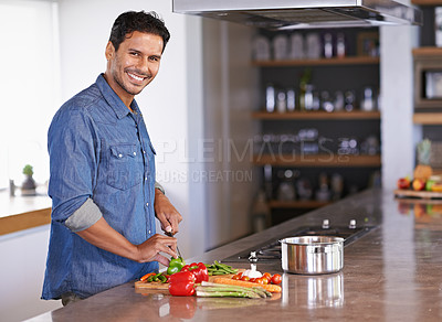 Buy stock photo Cropped view of a handsome young man chopping vegetables