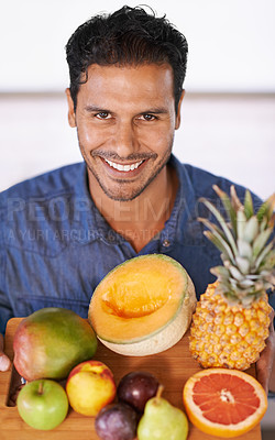 Buy stock photo Portrait of a handsome man holding up a chopping board full of fruit