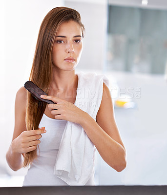 Buy stock photo Cropped shot of an attractive young woman using a flat iron