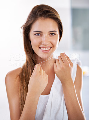 Buy stock photo Portrait of an attractive young woman holding dental floss and smiling