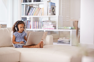Buy stock photo Shot of a little girl using headphones and a laptop while sitting at home