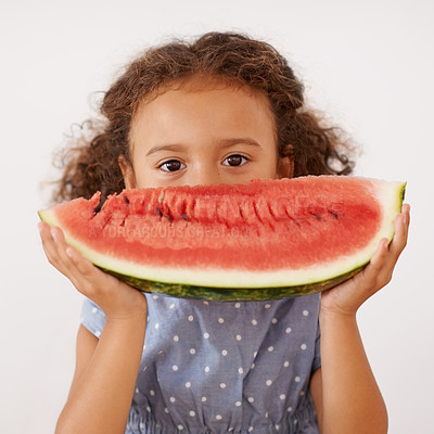 Buy stock photo Shot of a cute little girl holding a slice of watermelon in front of her mouth
