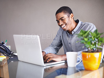 Buy stock photo Shot of a handsome young man happily working on his laptop at home
