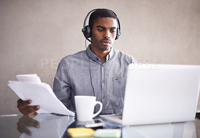 Buy stock photo Shot of a young businessman wearing a headset while working on his laptop at home