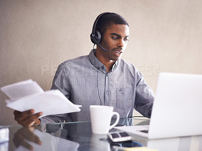 Buy stock photo A young businessman wearing a headset while working on his laptop at home