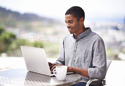Buy stock photo Shot of a handsome young man working on his laptop outside