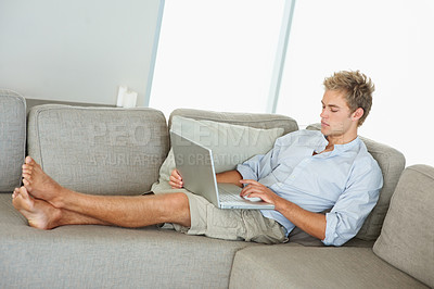 Buy stock photo Portrait of a young smart man working on a laptop