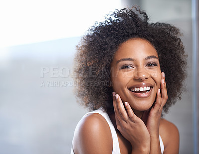Buy stock photo Portrait of an attractive young woman giving you a toothy smile while touching her skin