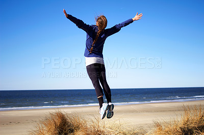 Buy stock photo Rearview shot of a young woman jumping into the air at the beach