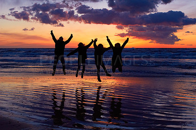 Buy stock photo Silhouette of a group of people jumping on the beach at sunset