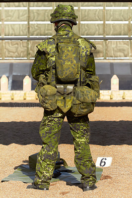 Buy stock photo Rearview shot of a young soldier in his uniform with his gear in front of him
