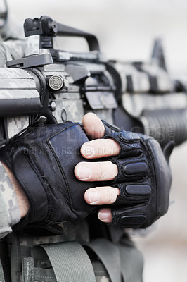 Buy stock photo Closeup cropped shot of the midriff of a soldier holding his gun against his chest