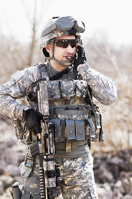 Buy stock photo A soldier crouched down next to a broken down wall and pointing his gun into the distance