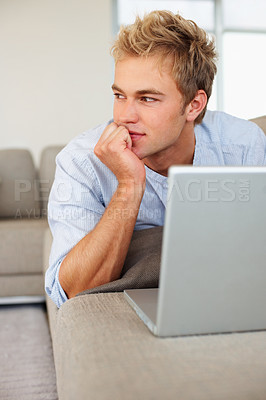 Buy stock photo Portrait of a young man working on a laptop